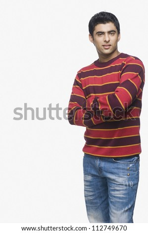 Young man standing with arms crossed - stock photo