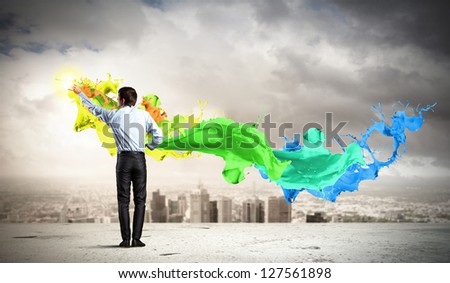young man standing with back painting splashes against city background - stock photo