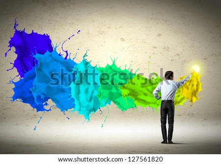 young man standing with back painting splashes with fingers