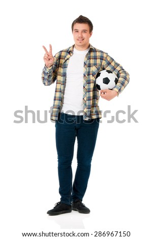 Young man standing with classic soccer ball showing victory sign isolated on white background - stock photo