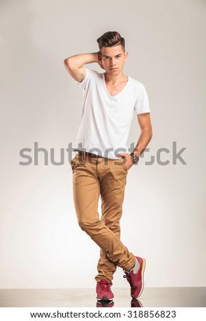 young man standing with legs crossed on beige studio background
