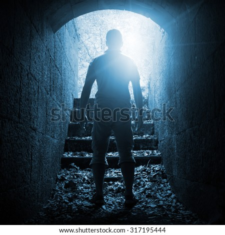 Young man stands in dark stone tunnel with glowing end, blue toned square photo - stock photo
