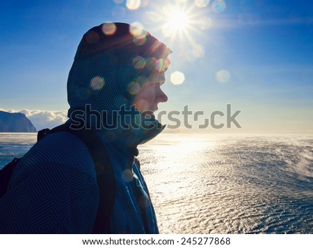 young man stands on a hill on a background of sea and sun - stock photo