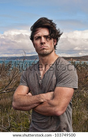 Young man stands on cliff top - stock photo