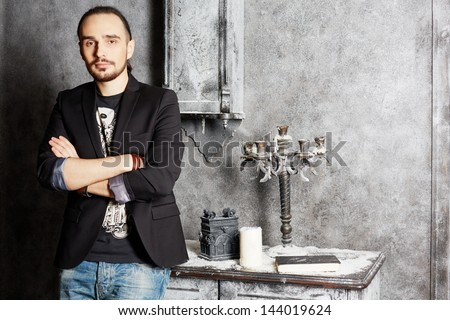Young man stands with arms folded leaning on old vintage table - stock photo