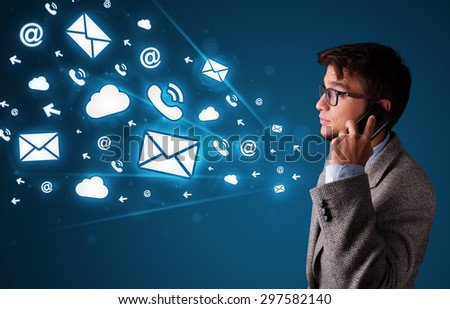 Young man staning and making phone call with message icons - stock photo