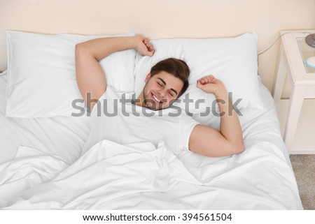 Young man stretching on bed in bedroom