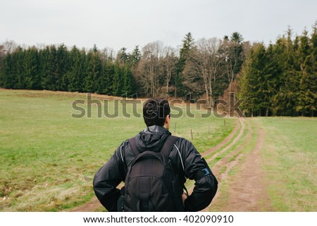 Young Man,Student hiking in forest.Man hiker back looking up enjoying nature during a trekking trip. Back of a young man outdoors in nature on a hiker path in forest. - stock photo