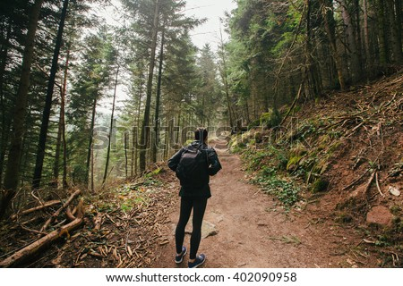 Young Man,Student hiking in forest.Man hiker looking up enjoying nature during a trekking trip. Back of a young man outdoors in nature on a hiker path in forest. - stock photo
