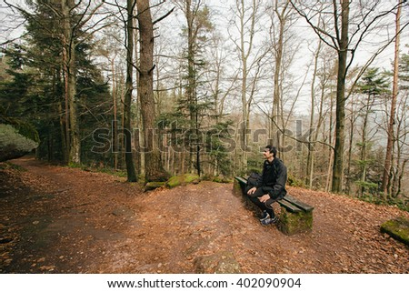 Young Man,Student hiking in forest.Man hiker smiling happy portrait looking up enjoying nature on a bench during a trekking trip.Young man outdoors in nature on a hiker path in forest. - stock photo