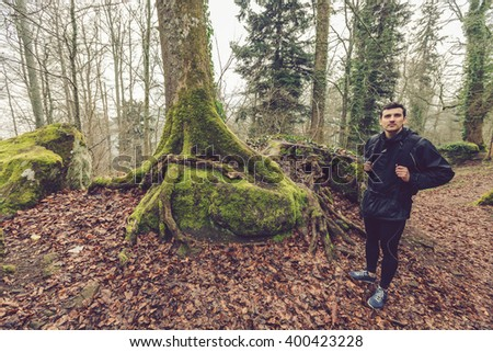Young Man,Student hiking in forest.Man hiker smiling happy portrait looking up on foggy day during a trekking trip. Back of a young man outdoors in nature on a hiker path in forest. - stock photo