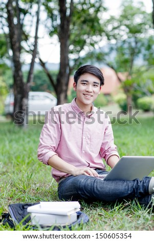Young man student sitting on the grass and work with laptop computer