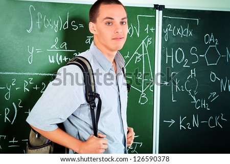 Young man student standing at the blackboard in the classroom.