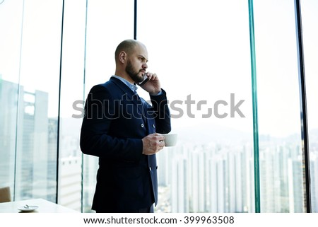 Young man successful entrepreneur in suit is phoning via his cell telephone during coffee break in work day, while is standing near office window with view of business district with tall skyscrapers