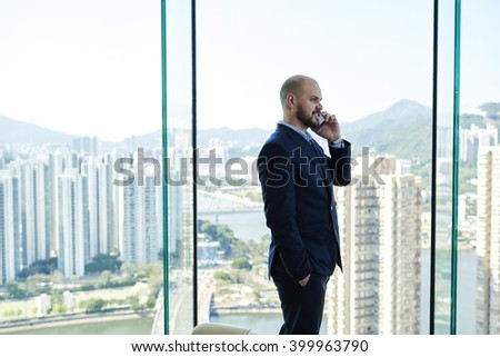 Young man successful entrepreneur is talking on mobile phone during break at work,while is standing in office interior near window with city view. Confident male manager is calling with cell telephone - stock photo