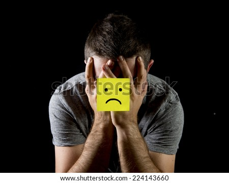 young man suffering depression and stress sitting alone in pain and grief feeling desperate with yellow note sad face stuck on his hands isolated on black background - stock photo