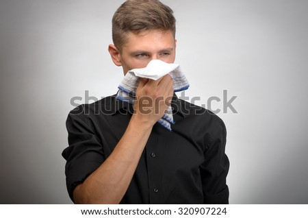 Young Man suffering from cold, Blowing His Nose - stock photo