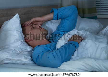 Young Man Suffering From Headache Lying On Bed In His Bedroom - stock photo