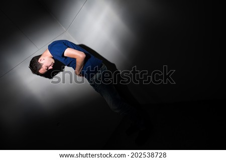 Young man suffering from severe belly pain, being cornered by the debilitating condition of celiac disease/Crohn's disease - stock photo