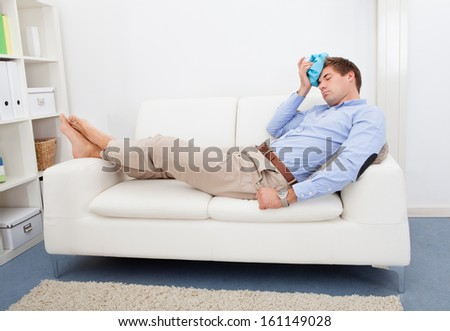 Young Man Suffering With Headache Applying Icepack - stock photo