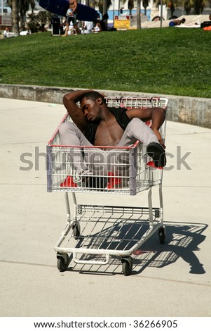 young man suffers from too much partying is in a grocery cart
