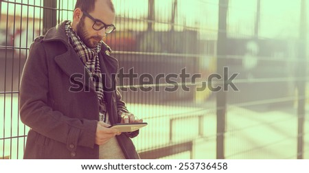 Young man surfing the internet on a tablet outdoor. Soft focus. - stock photo