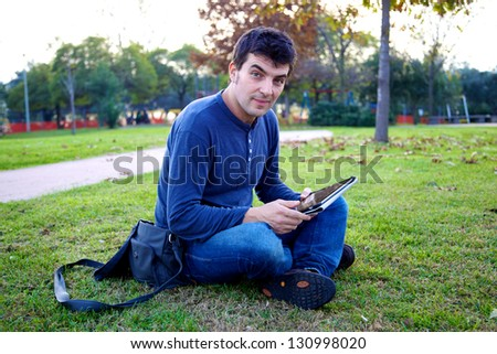 Young man surfing the web with electronic tablet in park during sunset