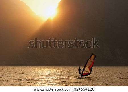 Young man surfing the wind during sunset - stock photo