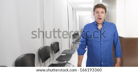 young man surprised in office or waiting room - stock photo