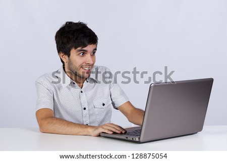 young man surprised with something he see on his laptop computer - stock photo