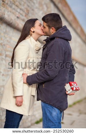 Young man surprising his girlfriend for Valentine's Day or birthday with a gift - stock photo