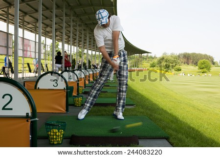 Young man sweeping ball on golf course - stock photo