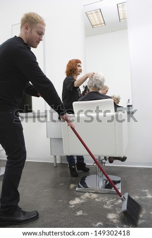Young man sweeping while hairdresser giving haircut to senior woman in salon - stock photo
