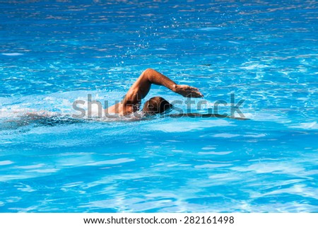 young man swim crawl style in outdoor swimming pool, sunny summer day - stock photo