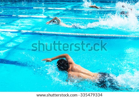 Young man swimming freestyle in a race. - stock photo