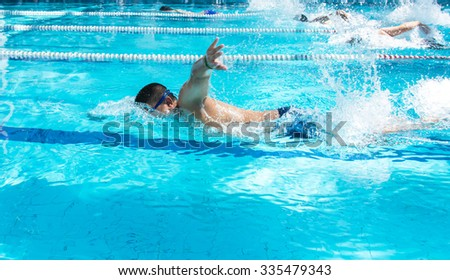 Young man swimming freestyle in a race.