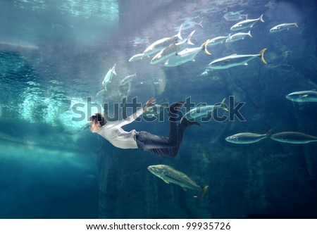 Young man swimming in a fish tank