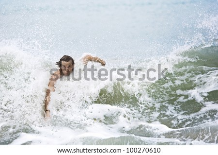 Young man swimming large ocean waves. - stock photo