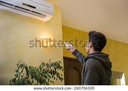 Young man switching on or adjusting the wall mounted air conditioner in the living room with a remote control - stock photo