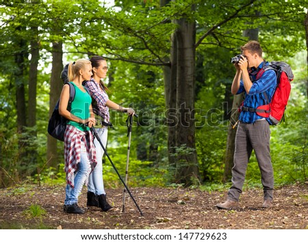 Young man take picture of his friends, while hiking