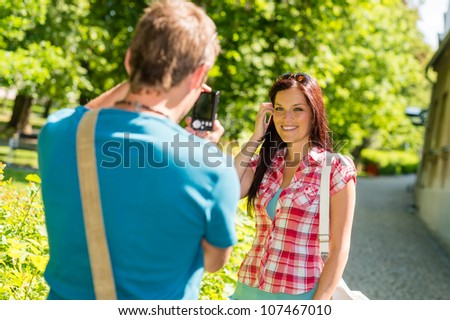 Young man take picture of his girlfriend outdoor city