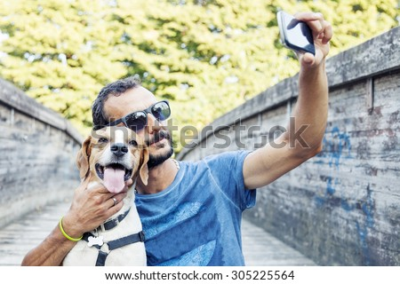 young man takes a selfie with his dog - stock photo