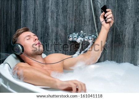 young man taking a bath, listening to music from the player