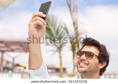 Young man taking a photo with his mobile phone - stock photo