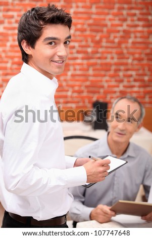 Young man taking an order in a restaurant