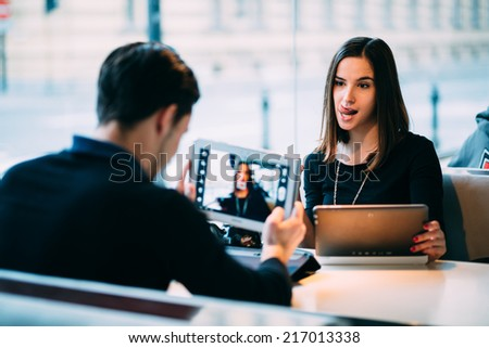 Young man taking photo of girlfriend with tablet computer in cafe - stock photo