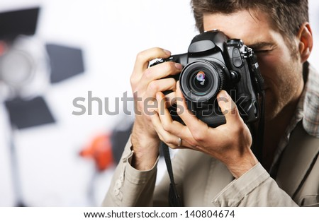 Young man taking photo with professional digital camera, focus on hand and lens - stock photo
