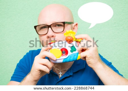 Young man taking photo with toy camera, focus on face