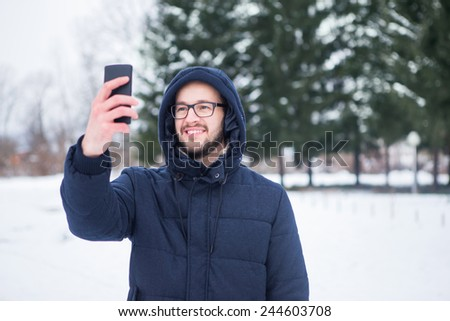 Young man taking selfie at winter day