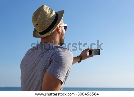 Young man taking selfie with mobile phone by the sea - stock photo